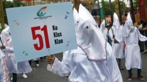 A troupe dressed in Ku Klux Klan costumes during Carnival holding a sign by the Ministry of Culture in Santo Domingo, Dominican Republic.